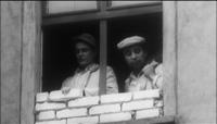 کارگرانی که پنجرههای ساختمانهای نزدیک دیوار را میپوشانند